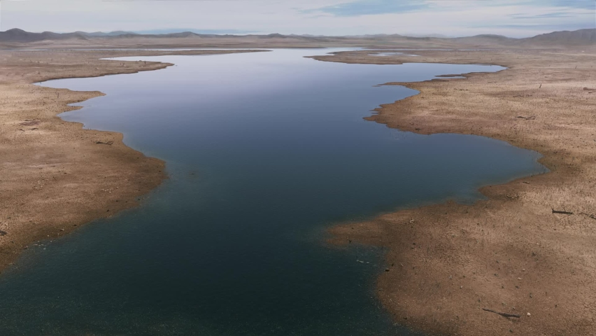 River and lake drying up, leaving the ground exposed. Arid riverbed, drought | Shutterstock HD Video #1060697569