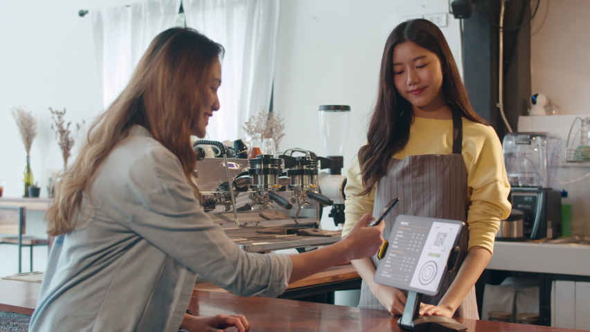 Young Asia female self service use mobile phone pay contactless with tablet at cafe restaurant. Girl barista talking receive orders from customer at bar counter in coffee shop. Owner small business. Royalty-Free Stock Footage #1060698730