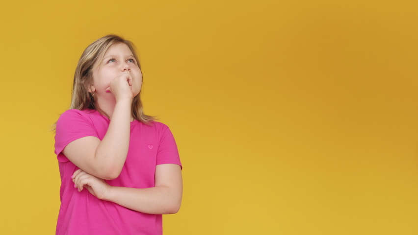 Pensive child. Problem solution. Inspiration choice. Confused doubtful young chubby girl in pink t-shirt thinking pointing up agree with idea isolated on yellow copy space background.