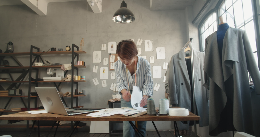 Hipster asian clothes designer working with her sketches, drawing them on graphics tablet, designing her new collection - small business, fashion concept 4k footage | Shutterstock HD Video #1060702648