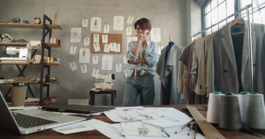 Authentic female fashion designer wandering around her office, looking for inspiration for new collection - fashion, small business, art concept 4k footage | Shutterstock HD Video #1060702654