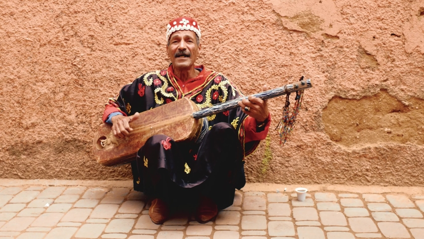 Marrakech, Morocco, March 2020, guitar player sings in the alleys of the medina