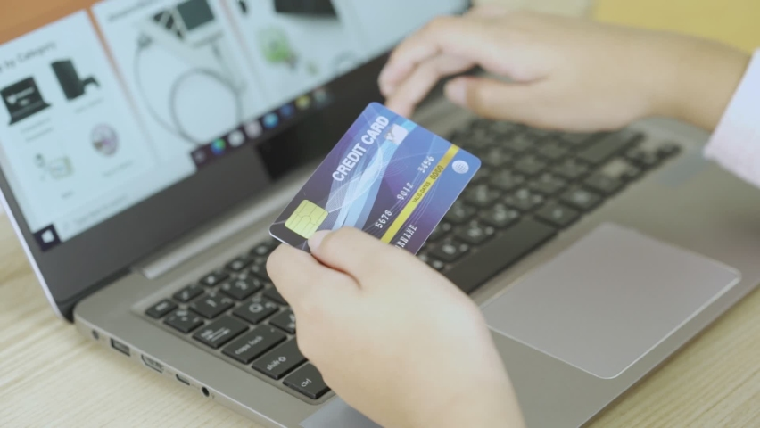 Close up young woman hold credit card use notebook computer typing number payments at home. Zoom hand girl customer purchase, shoping online food delivery, hotel booking, buy application by laptop Royalty-Free Stock Footage #1060712689