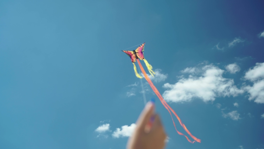 Hand holds butterfly shape kite on bright sunny summer day. Holiday and childhood. You are in control. Colorful kite flying in the wind   Shutterstock HD Video #1060712800