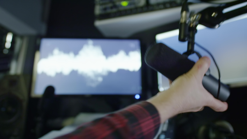 Microphone in a radio studio. DJ moves the microphone, starts broadcasting hot news. Records an evening podcast. Equipment in a recording studio. Sound wave, equalizer Royalty-Free Stock Footage #1060714849
