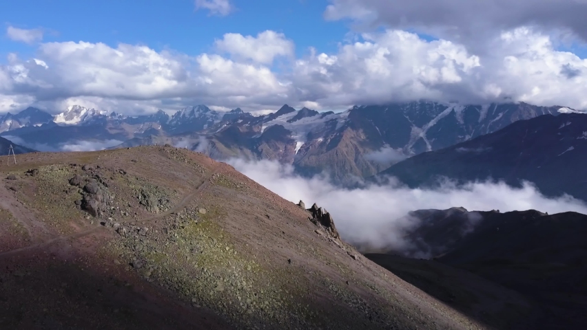 Mountain range in clouds on blue sky background. Clip. View from the mountain peak on amazing endless high hills and white flowing clouds, beauty of nature. Royalty-Free Stock Footage #1060720408
