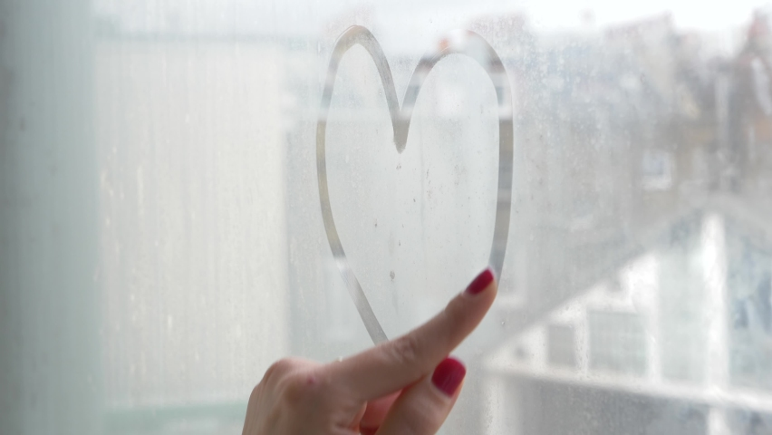 Woman drawing heart shape on the window with her finger - alone young woman draw on wet glass of the window on a moody day isolating at home   Shutterstock HD Video #1060720447