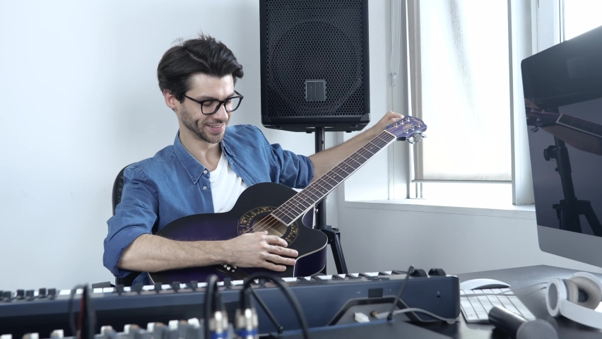 Young man in sound recording studio. Guy sit at table with mixing console on it and play on acoustic guitar. Recording sound alone in studio.   Shutterstock HD Video #1060726879