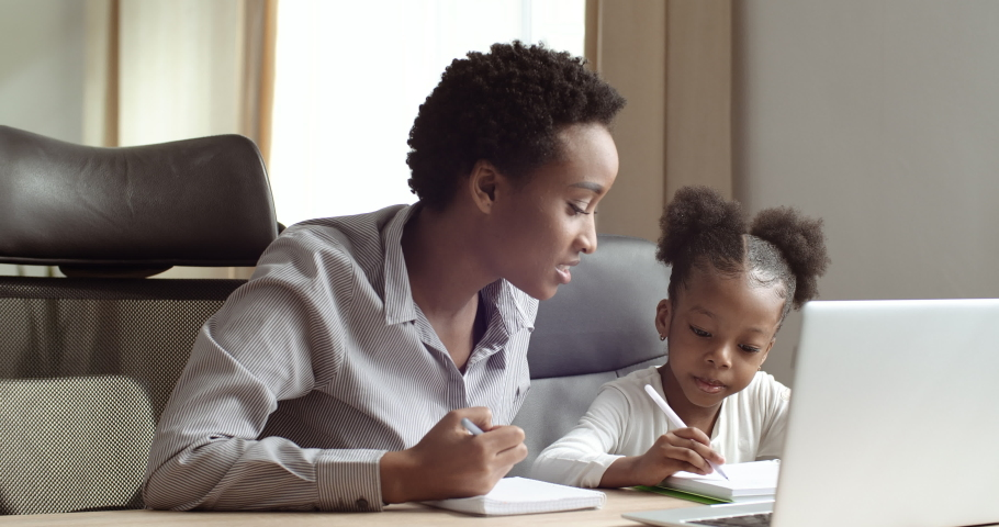 Cute small 6-7 years african kid daughter learning writing with young mixed race mom tutor. Adult parent mother teaching school child girl helps with homework studying sitting at table, home education Royalty-Free Stock Footage #1060727125