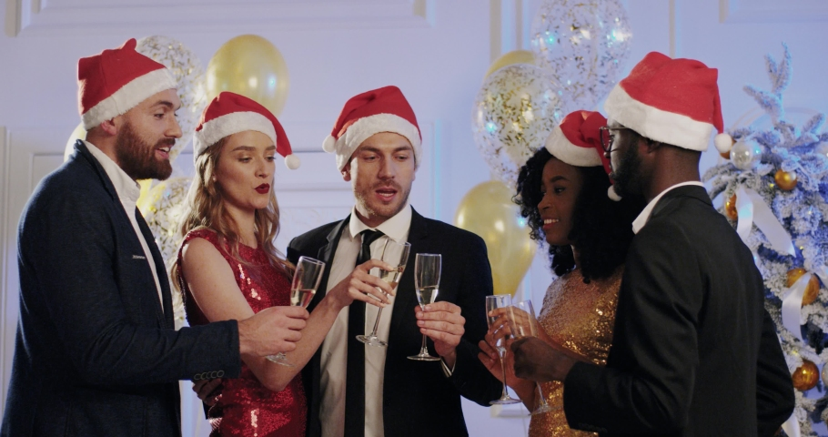 Cheerful company of colleagues communicate together at New Year's corporate party. Multiethnic group of people knocking glasses with champagne on Christmas decor background. Royalty-Free Stock Footage #1060733530
