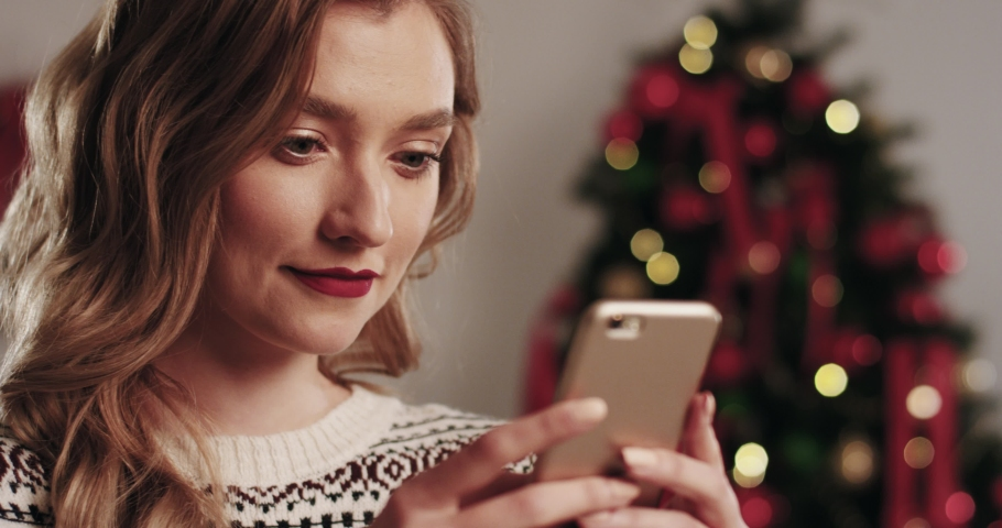 Portrait of young beautiful blonde woman in winter sweater typing message on mobile phone and reacting emotionally receiving good news. Royalty-Free Stock Footage #1060733599