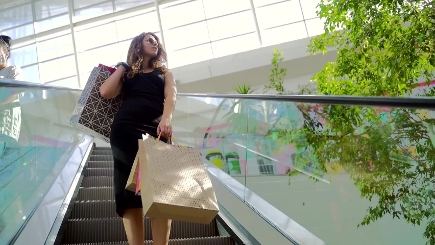 Stylish young woman in black dress and sunglasses lifting up on escalator with colorful shopping bags. Attractive brunette spending leisure time at big modern mall. Royalty-Free Stock Footage #1060738294