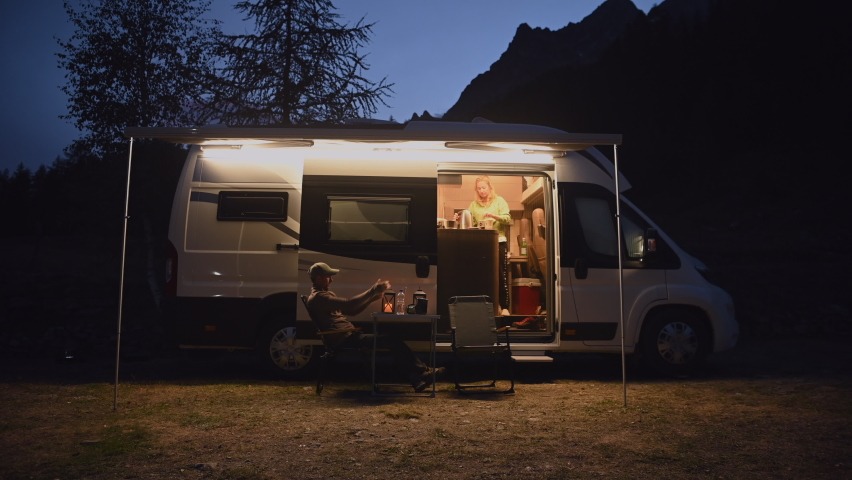 Caucasian Men Working Remotely From Scenic Camping Using His Laptop and LTE Connection While Seating in Front of His Camper Van. Royalty-Free Stock Footage #1060739794