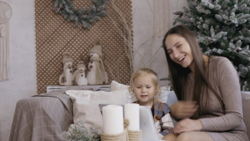 Mother and daughter make video call via pad on Christmas morning. Young mom with her little daughter congratulate their relatives a happy new yaer. Royalty-Free Stock Footage #1060741036