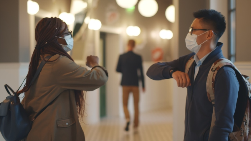 Multiethnic students in mask greeting with elbow bumps keeping social distancing Royalty-Free Stock Footage #1060746979