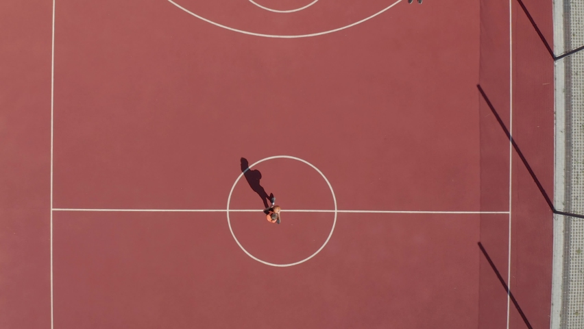 Aerial Shot of Basketball Court. Aerial view of basketball player approaching and scoring a hoop.