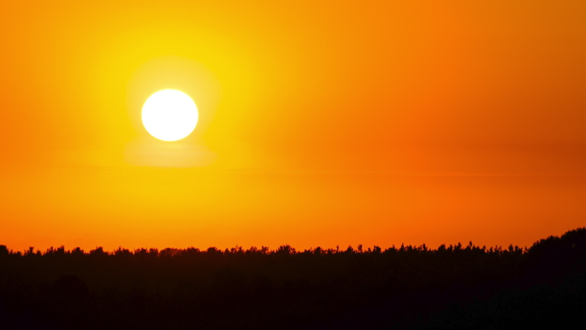 Sunset in the Yellow Sky. Timelapse. Big bright Yellow sun moves down. Awesome landscape of sky and silhouette of forest on the horizon. Amazing colors of the setting sun. Vibrant color. Time Lapse
