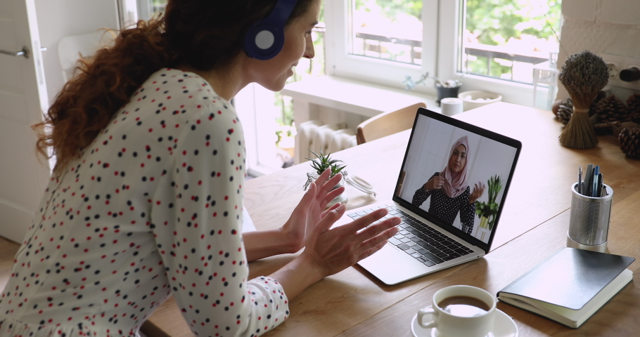 Multiracial businesswomen negotiate using laptop and video call app, screen view where female in hijab talks with colleague, businesspeople work distantly solve issue share thoughts at virtual meeting Royalty-Free Stock Footage #1060757536