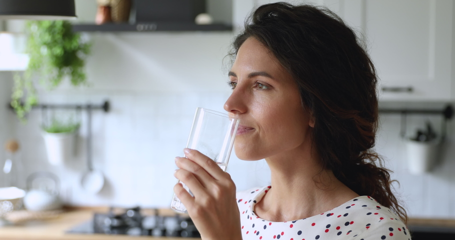 Thirsty smiling 35s woman standing alone in domestic kitchen start new day with healthy life habit, holding glass drinking clean mineral natural still water close up view. Lifestyle healthcare concept Royalty-Free Stock Footage #1060757560