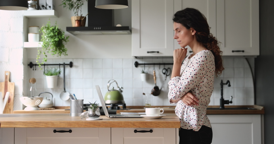 Woman standing in home cozy kitchen use laptop do freelance work looking focused deep lost in thoughts, thinking solving issues distantly makes research, author writing creative work online concept Royalty-Free Stock Footage #1060757575
