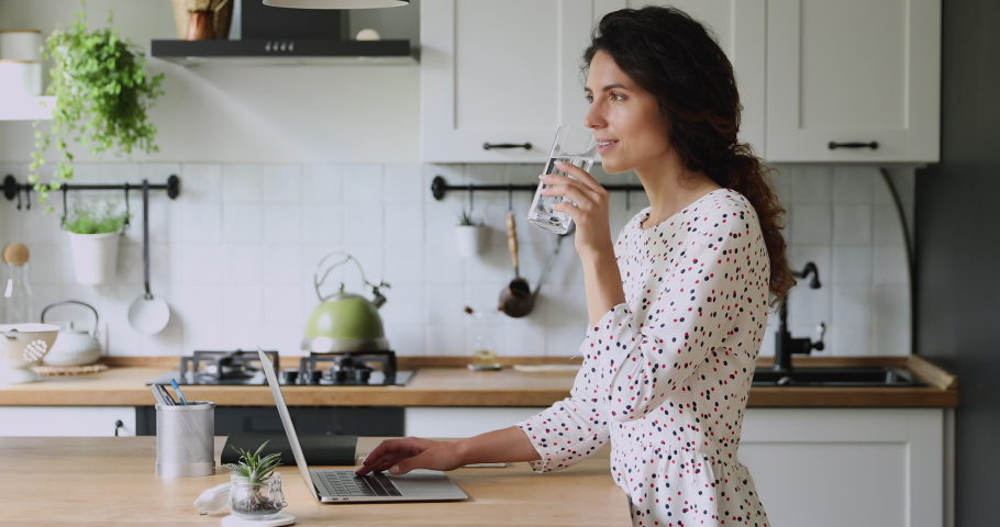 Woman standing in kitchen working on laptop do freelance remote job texting message take break drink natural mineral water makes sip caring about health, prevents dehydration. Everyday routine concept Royalty-Free Stock Footage #1060757581