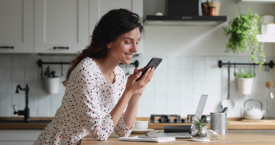 Smiling millennial 35s woman standing in kitchen holding mobile phone looks at screen scroll photos in social media network, spend time on internet websites, choose goods in fashion e-stores at home. Royalty-Free Stock Footage #1060757602