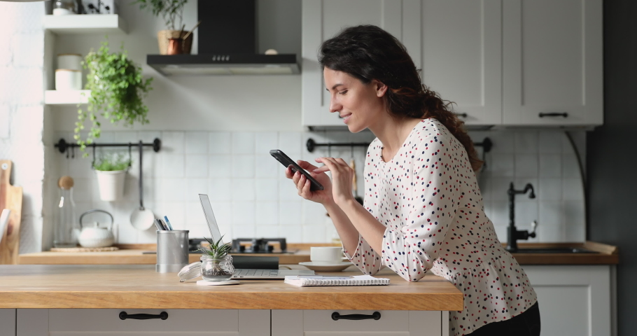 Woman resting standing in kitchen lean at dining table hold smartphone choose goods on internet, make food delivery order on-line. Modern wireless tech simplifies life, easy e services usage concept Royalty-Free Stock Footage #1060757611