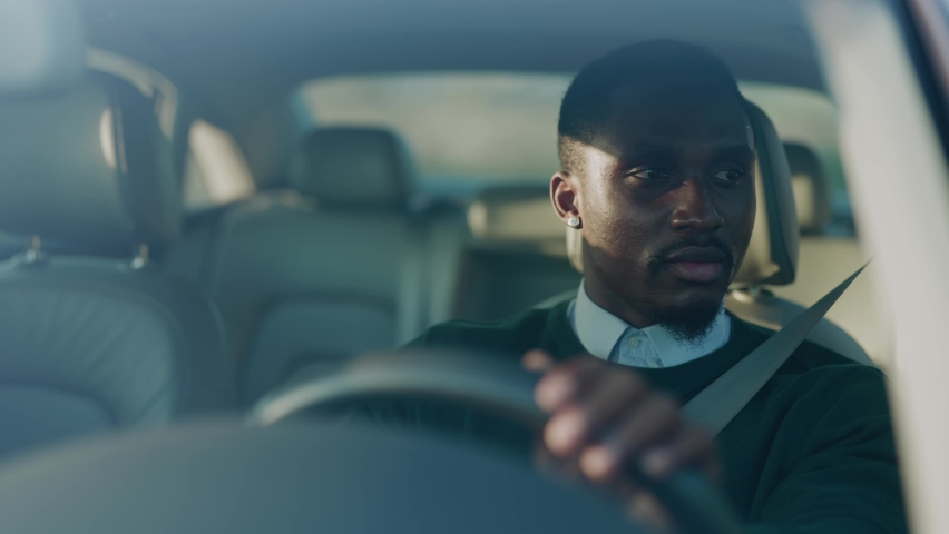 Attractive young african american man driving car with passenger. Serious man at sunlight. Automobile businessman traffic transportation. Slow motion Royalty-Free Stock Footage #1060757674
