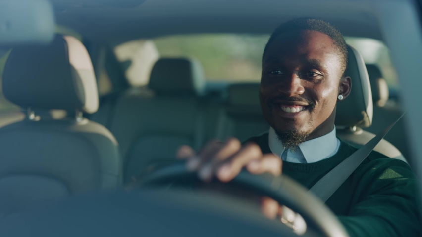 Funny young african american man smiling driving car with passenger. Feel happy at sunlight. Automobile businessman traffic transportation. Slow motion