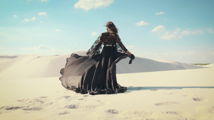 Silhouette of a woman in a black dress with a long train. The fabric flies in the wind. A girl walks in the desert. Fashion model rear view. White sands of Volnogorsk city, Ukraine Royalty-Free Stock Footage #1060757947