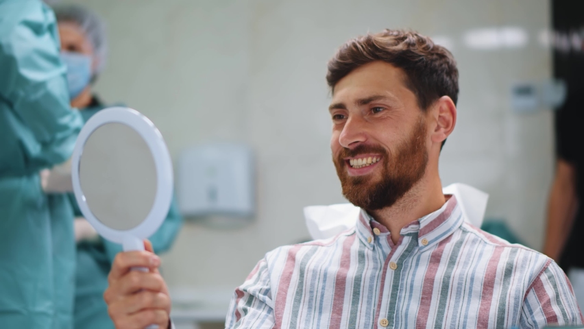 Handsome cheerful young male patient smiling into mirror looking at healthy white teeth enjoying dental healthcare facilities in modern dentist office. Royalty-Free Stock Footage #1060758316