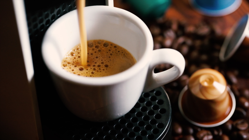 Automatic coffee machine with coffee capsules or coffee pods pouring espresso drink   Shutterstock HD Video #1060758898