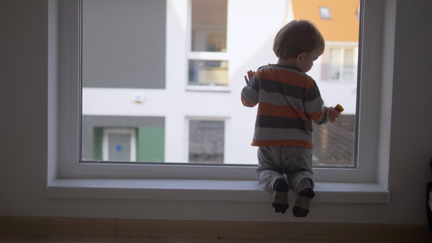 Little baby child on his knee look outside on window, waiting to go outdoor | Shutterstock HD Video #1060758988