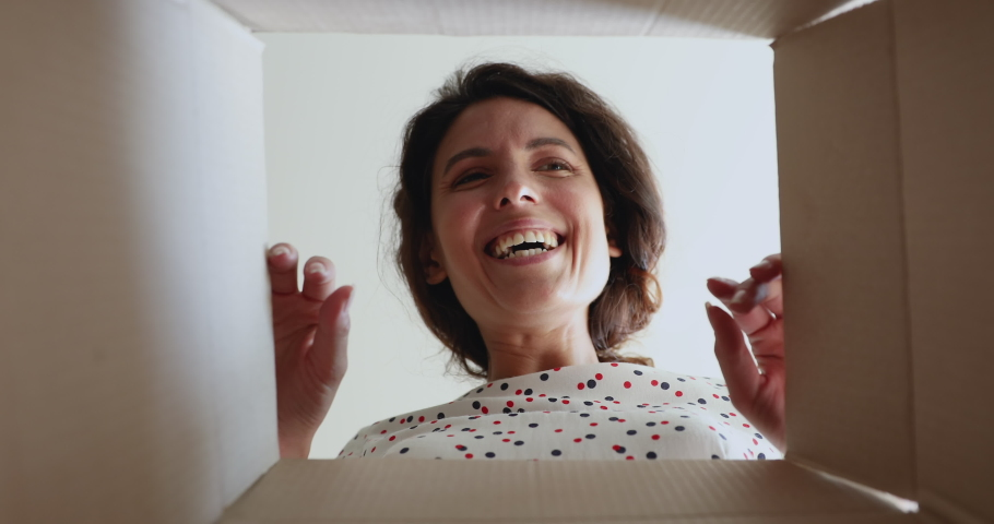 Close up inside of carton box bottom view, woman opens parcel looks at delivered goods items feels happy. Satisfied client, positive feedback. Buy in e-commerce web stores, express delivery concept Royalty-Free Stock Footage #1060760143