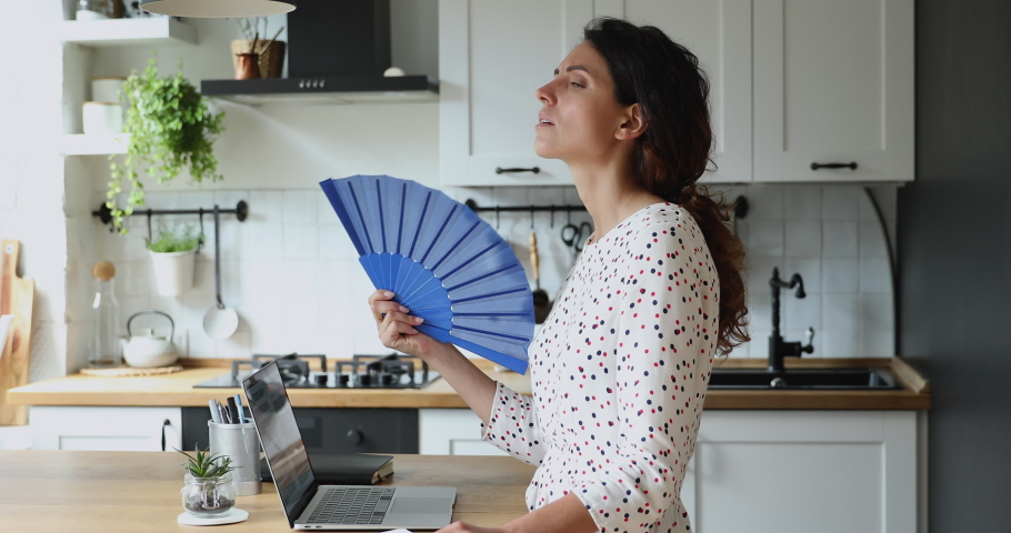 30s female standing in kitchen distracted from work on laptop suffers from high temperature indoor at hot summer day feels discomfort wave blue fan cools herself. Home without air conditioner concept