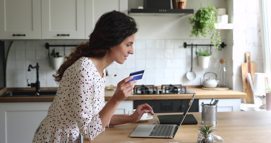 Woman standing in domestic kitchen using portable computer enter credit card numbers buying on internet, booking hotel. Housewife paying for food delivery order, secure easy electronic payment concept