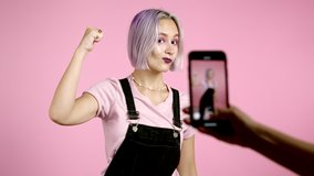 Smiling vlogger hipster woman recording video of herself dancing in front of smartphone camera on pink background. Influencer makes funny social media clip
