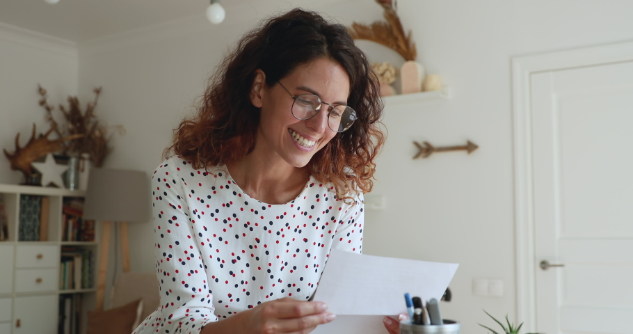 Woman in glasses received mail correspondence take out letter from envelope read enjoy pleasant news. Got invitation on event, bank loan approved, career growth and advance, promotion at work concept