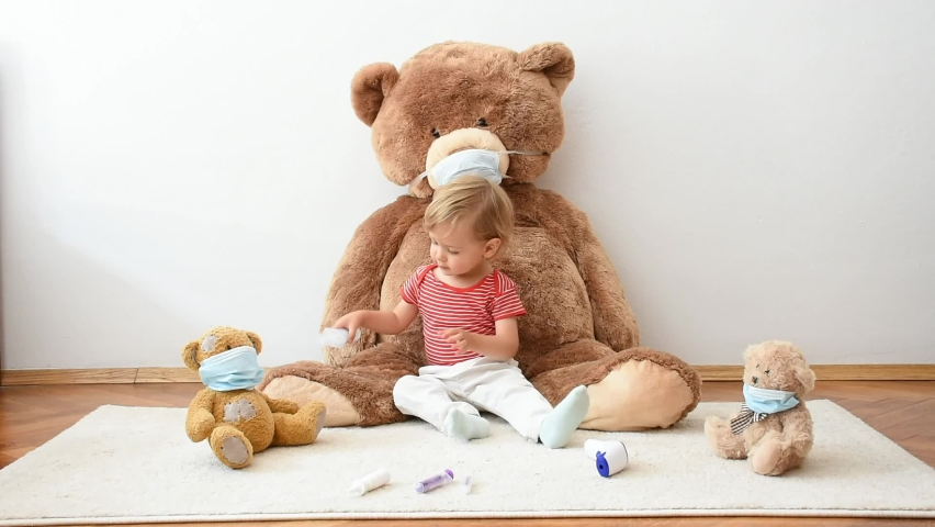Cute little child playing with his sick teddy bears wearing medical mask against viruses. Role playing, child playing doctor with plush toy. Children and flu, coronavirus illness concept.