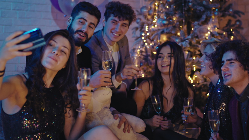 Group of mature beautiful friends at Christmas party celebrating together beside the Christmas tree they take selfies for memories. Shot on ARRI Alexa Mini | Shutterstock HD Video #1060769914