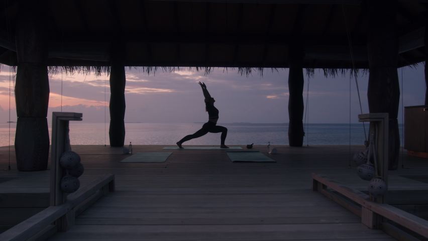 Zoom in shot of a woman in sportswear practicing yoga in a stilt house at a beach resort. Woman doing yoga at in overwater bungalow.