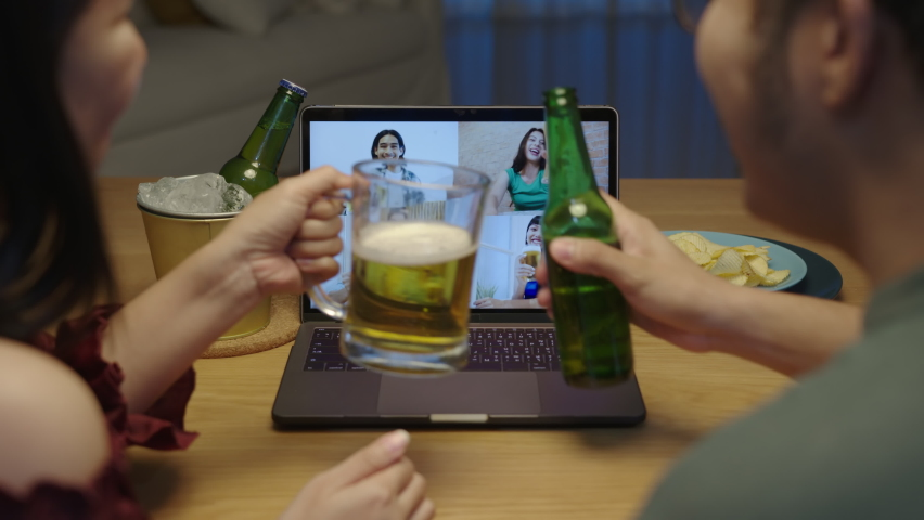 Zoom out : Young happy asian couple enjoy relax night party event online celebration festive with friends at home clinking beer with glass and bottle toasting drinking via video call. Royalty-Free Stock Footage #1060771444