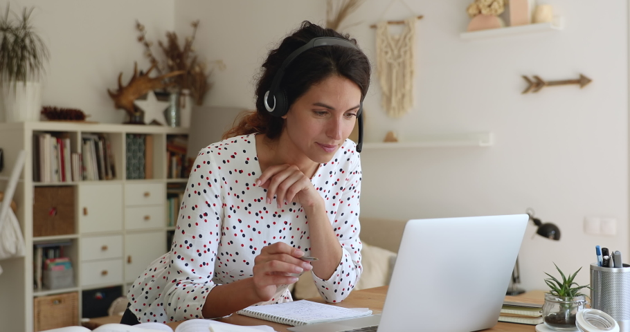 35s woman lean at table wear headset looks at laptop screen writing down received information, listen e-teacher, gain new knowledge by videocall. Take part in webinar conducted over internet concept Royalty-Free Stock Footage #1060771897