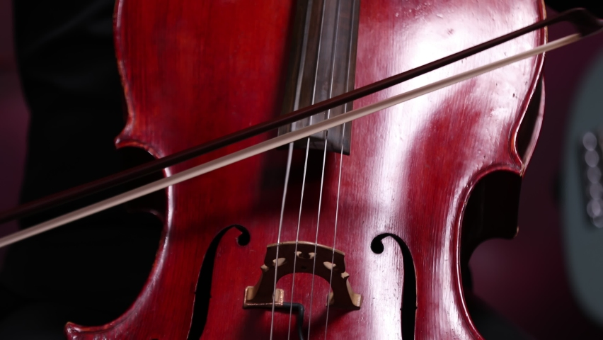 A man hand playing cello. Male solo musician playing violoncello in orchestra. Classical music pattern | Shutterstock HD Video #1060774483