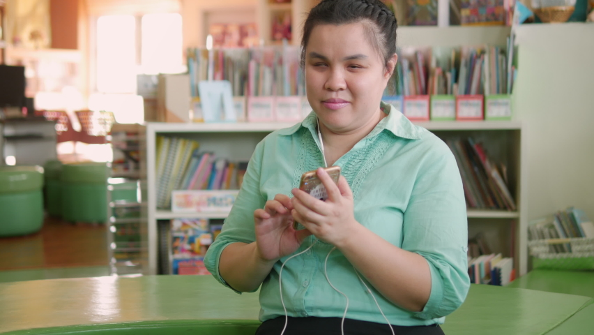 Portrait of Asian young blind person woman enjoy using smart phone with voice accessibility for persons with disabilities in creative workplace. Royalty-Free Stock Footage #1060775974
