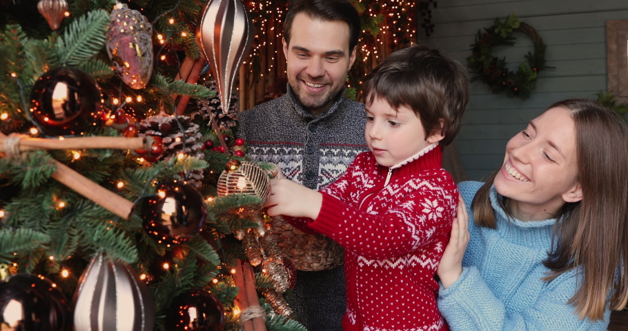 Happy family preparing for New Year winter holidays celebration concept. Young 30s couple his preschool adorable 5s son decorating Christmas tree create festive mood atmosphere at modern cozy house Royalty-Free Stock Footage #1060777426