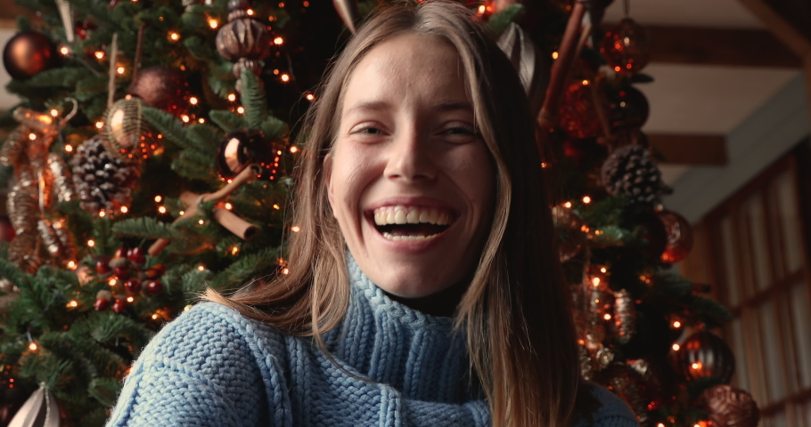 Close up web cam view happy 25s woman making x-mas eve video meeting conference congratulating relatives family remotely, sit at home near twinkled lights decorated Christmas tree, modern tech concept Royalty-Free Stock Footage #1060777438