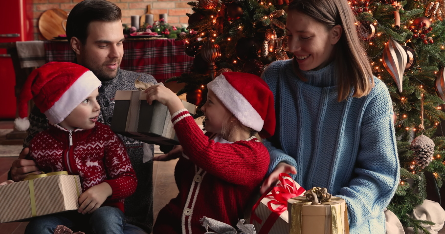 Happy family with little daughter and son in Santa hats gathered together on Christmas morning near xmas tree chatting enjoy gifts opening. New Year celebration, presents store advertisement concept Royalty-Free Stock Footage #1060777483