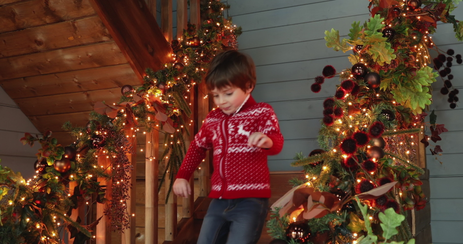Lush garland with twinkle lights and leaves decor house stair railing view, excited kids wear winter sweaters run downstairs to receive prepared Christmas gifts. New Year holidays celebration concept | Shutterstock HD Video #1060777486