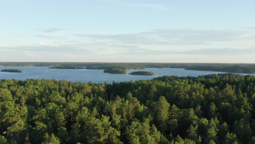 Swedish archipelago in aerial drone shot flying over forest and islands. Swedens most beautiful nature overview shot. Trees and green woods on warm summer evening close to Stockholm city Royalty-Free Stock Footage #1060777525